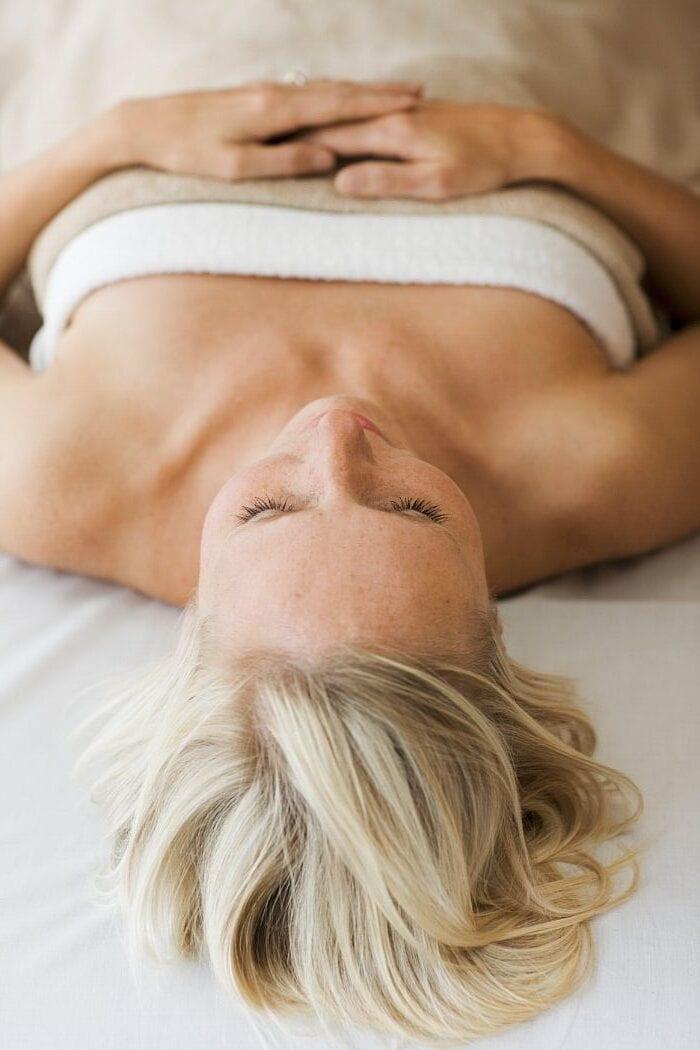 Kvinde ligger afslappet på massagebriks