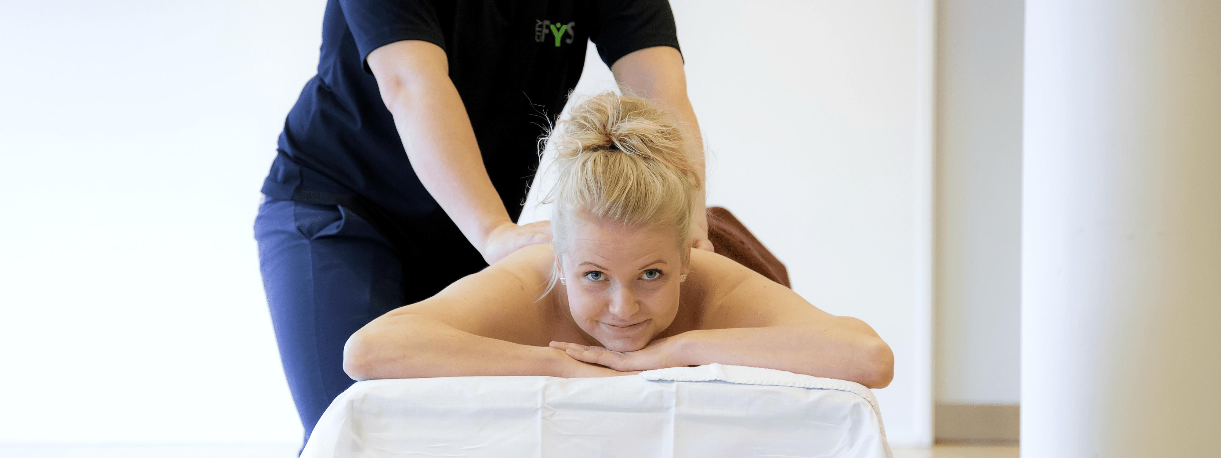 Kvinde kigger op mens hun bliver masseret på ryggen