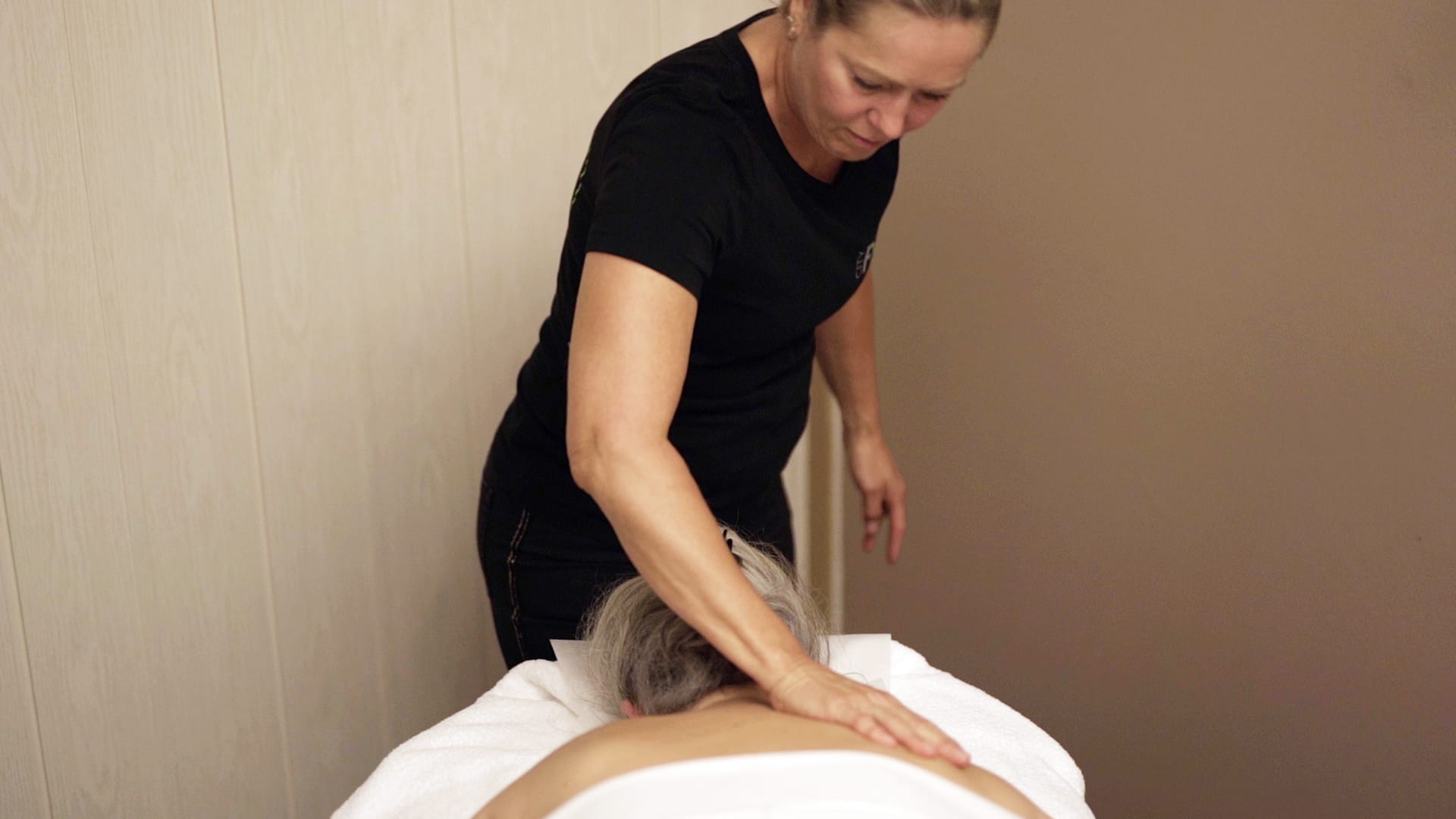 Massør giver massage på skuldre
