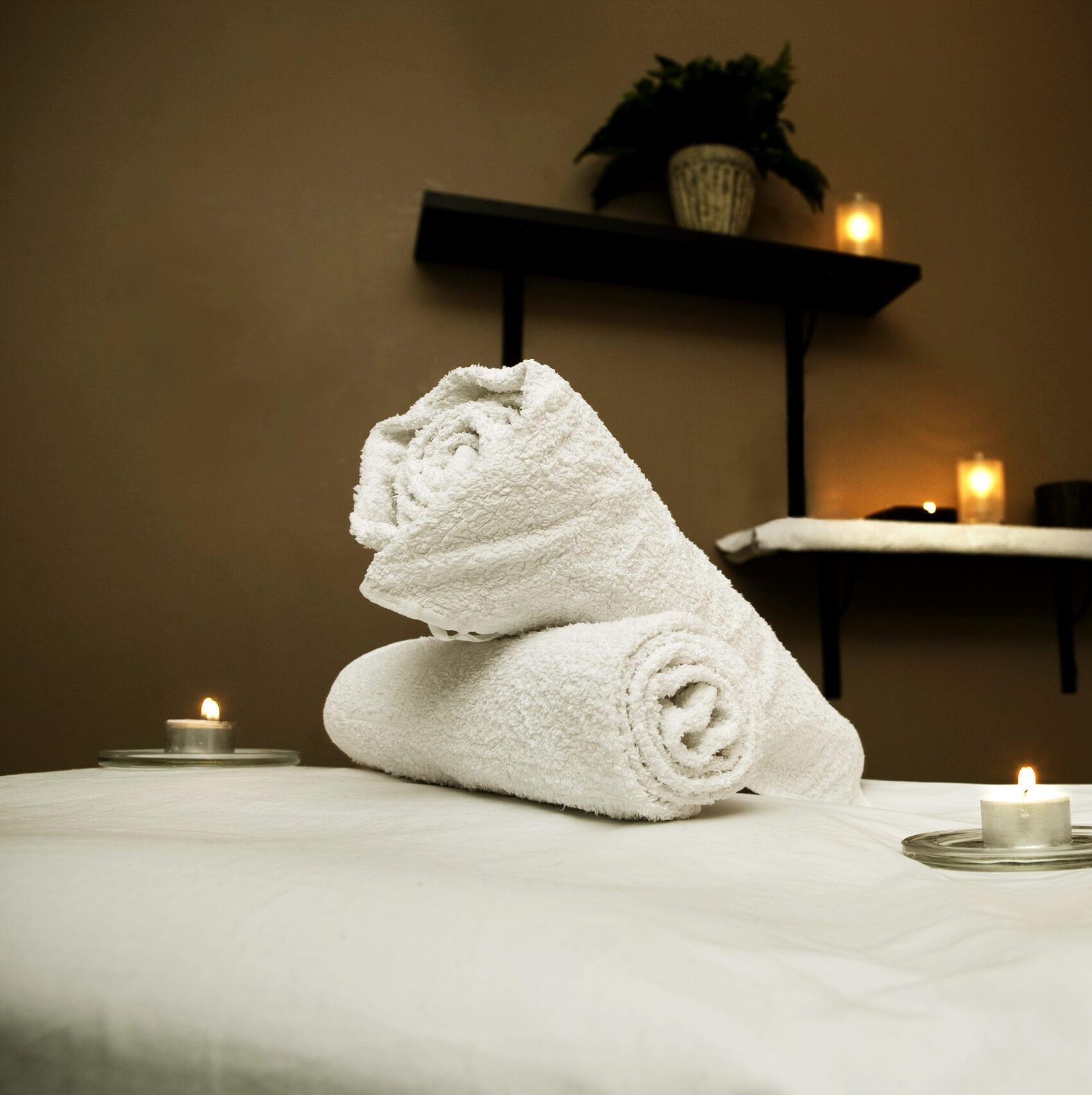 Massagebriks med rullede håndklæder og lys
