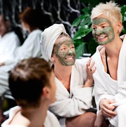 Kvinder som sidder med ansigtsmaske