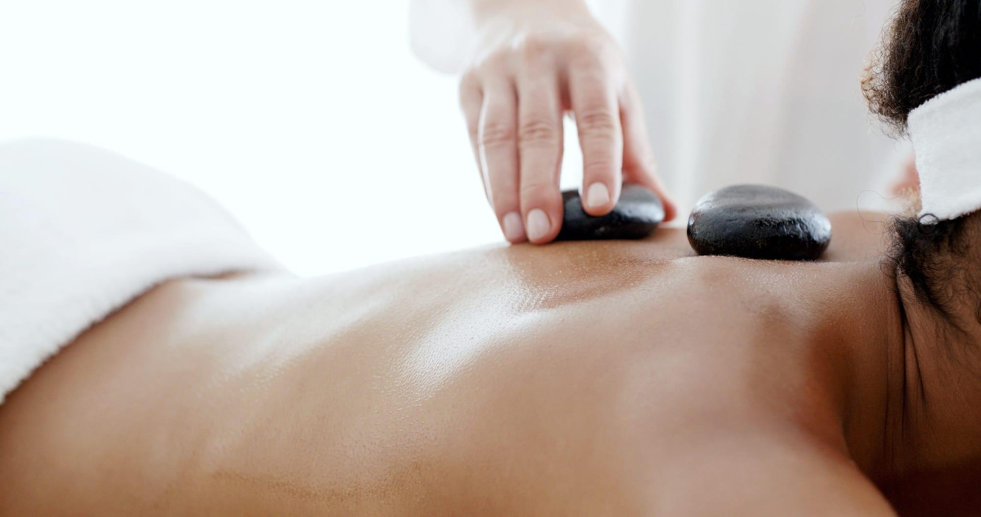Massage med varme sten på ryggen