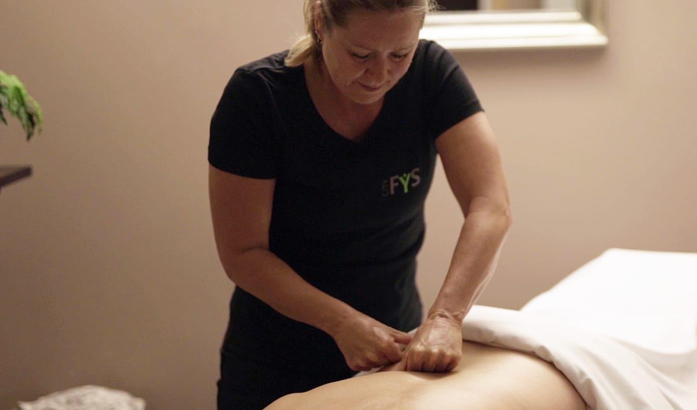Fysioterapeut giver behandling på kunde