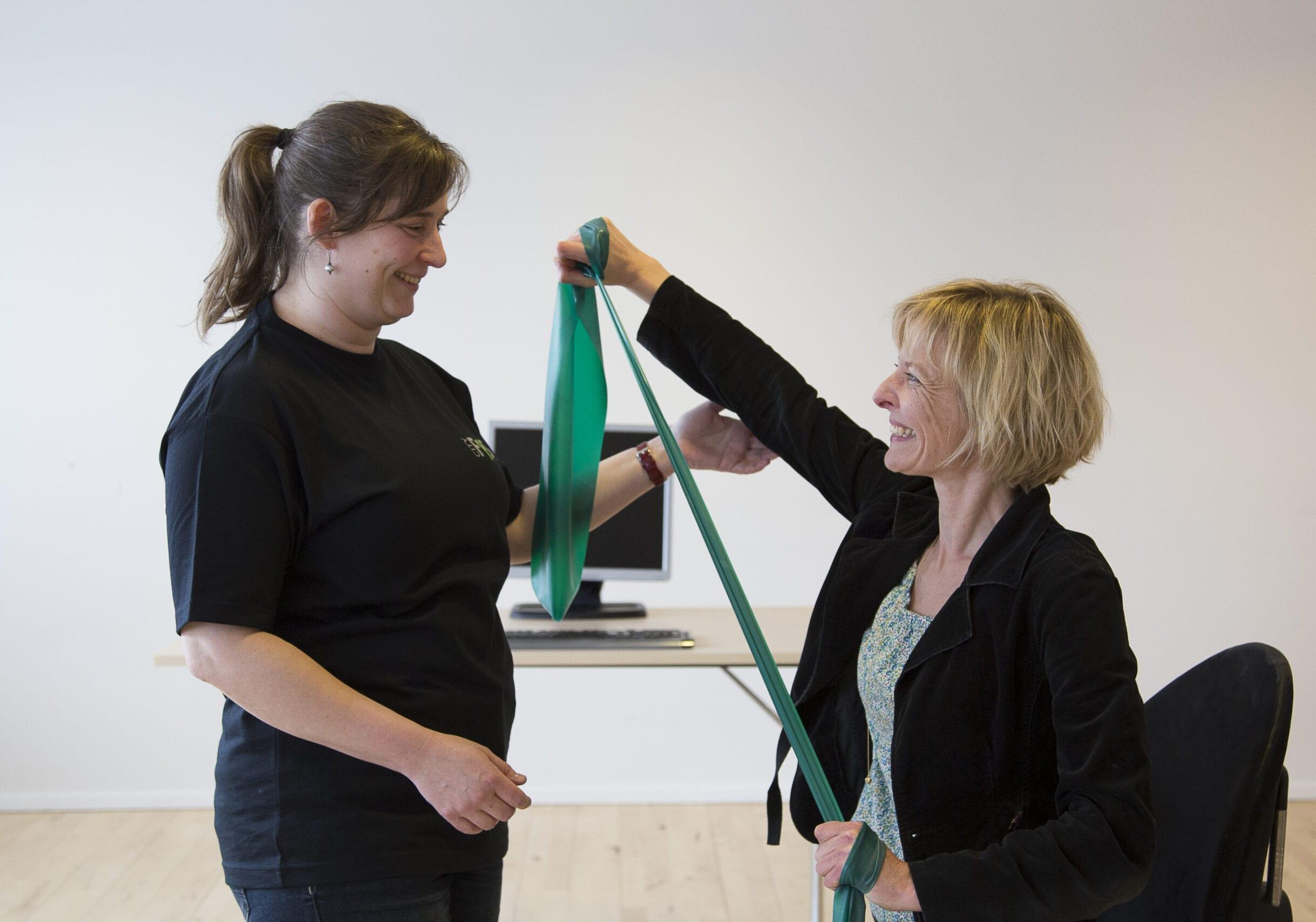 Konsulent viser øvelser med elastik